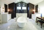 A white, tiled bathroom. The bathtub sits prominently in the center of the room. very well lit, with white marble and black tile in the background